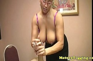 Busty mature tugging a younger cock